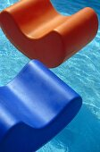 Orange and blue plastic floating chairs in outdoor swimming pool