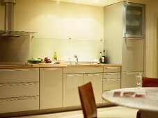 Round table and chairs in kitchen with cream cupboard units and wooden worktops.