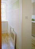 A detail of a partition wall separating a kitchen from another room, wooden floor,