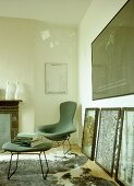 Retro style chair and footstool next to large pieces of artwork propped against wall