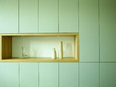 Light green units with glass vase and pottery vases in recess