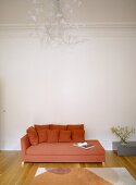 A detail of a modern, sitting room with a red upholstered sofa, chaise longue, wood floor, side table, chandelier light,