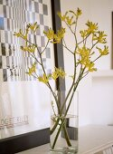 A detail of an arrangement of yellow flowers in a glass vase, black and white print in frame placed on mantelpiece,