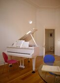 A detail of a music room, a white piano, red retro chair, wood floor, glass table, door open,