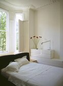 A modern bedroom in neutral colours, a double bed with upholstered headboard, bed linen, bay window with shutters, traditional room with period detail