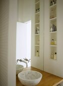 A detail of a modern bathroom in neutral colours, marble washbasin set on wooden shelf, built in shelving, taps, mirror, toiletries,