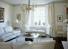 A traditional, neutral sitting room with upholstered sofas, glass coffee table, curtains, chandelier