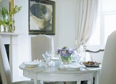 A detail of a traditional, neutral dining room with painted wooden table and upholstered chairs