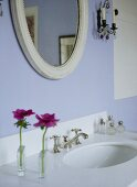 A detail of a modern, pale blue bathroom showing washbasin set in unit, oval mirror, glass perfume bottles, styled