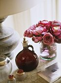 A display of items on a table including a vase of pink roses, a stone lamp, a silver box and a glass bottle