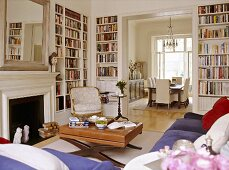 A traditional sitting room with fireplace and built in book shelves, with an open doorway leading to a dining room