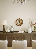 A detail of a traditional, neutral dining room with a wood sideboard, upholstered chairs, modern ceramic pieces
