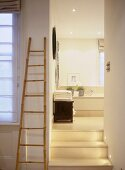 A view of steps leading to a modern en-suite bathroom, bath