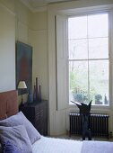 Bedroom with ornaments and sculpture under window with shutters.