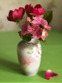 Flowers with pink blossoms in a porcelain vase on a green surface