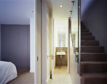 A view from a stairwell through an open door in to a bedroom and a bathroom