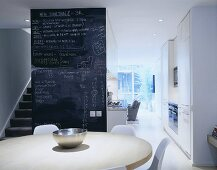 A dining room in an open-plan living room-cum-kitchen and a floor-to-ceiling blackboard next to a flight of stairs