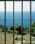 Blick durch das Fenster in den Garten und auf das Meer