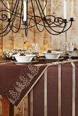 Weihnachtlich gedeckter Tisch in Braun, darüber Kerzenleuchter aus Eisen