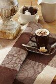 Eine Tasse Cappuccino auf braun karierter Tischdecke