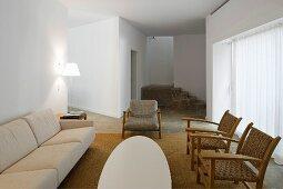 Offener weisser Wohnraum mit hellem Sofa und rustikalen Sesseln