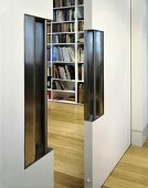 A half open sliding door with an integrated, stainless steel handle and a view of a bookshelf