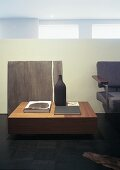 A walnut coffee table, books, a ceramic bottle and an acrylic painting by Ad