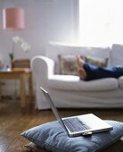 A laptop on a cushion in a living room with a woman in the background laying on a sofa