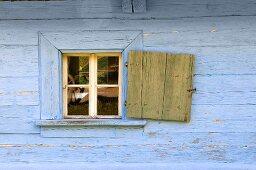A blue wooden hut with an open window shutter