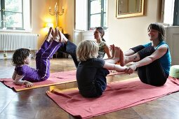 Mothers and children practising yoga
