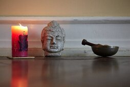 Candles, a Buddha hand and a singing bowl in a yoga studio