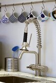 Cups hanging from hooks above a kitchen tap