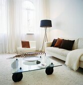 A floor lamp next to a white sofa and a glass coffee table in a living room