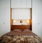 A double bed with built-in cupboards and a built-in bedside table on the headboard