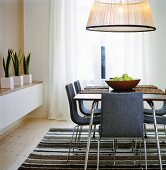 A large pendent lamp above a dining table and chairs