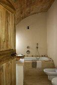 Blick durch eine geöffnete Holztür in das Badezimmer