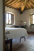 Blick in ein Schlafzimmer mit Terrakottaboden und Holzbalkendecke
