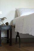 Ein Nachttisch neben einem erhöhten Bett mit weisser Bettwäsche