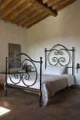 Ein Bett mit schmiedeeisernem Gestell in einem Schlafzimmer