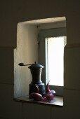 Eine alte Kaffeemühle und Zwiebeln in einer kleinen Fensternische