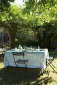 Gedeckter Tisch unter einem Baum im Garten