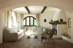 Ein Wohnzimmer mit Sitzmöbeln, Kamin und Terrakottaboden