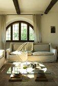 Ein niedriger Wohnzimmertisch mit Glasplatte vor einem Sofa