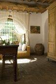 Ein Esstisch mit Stühlen und ein Rattansofa vor dem Bogenfenster in einem Esszimmer