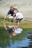 A father and a daughter play in a lake