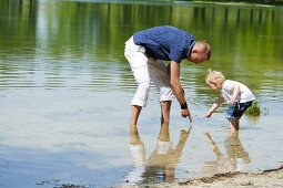 A father and his daughter playing in a lake