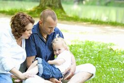 A young family sitting on the grass by a lake