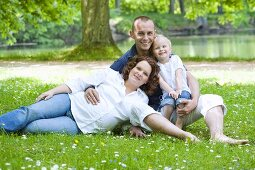 A happy young family lying on the grass by the lake