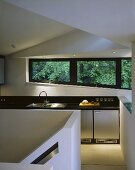 An open plan designer kitchen with windows looking onto trees