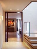 Lobby with contemporary staircase and view through an open door into a living room